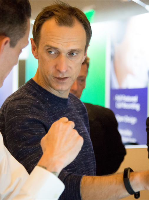 Nextiva CEO Tomas Gorny discussing work with an employee.