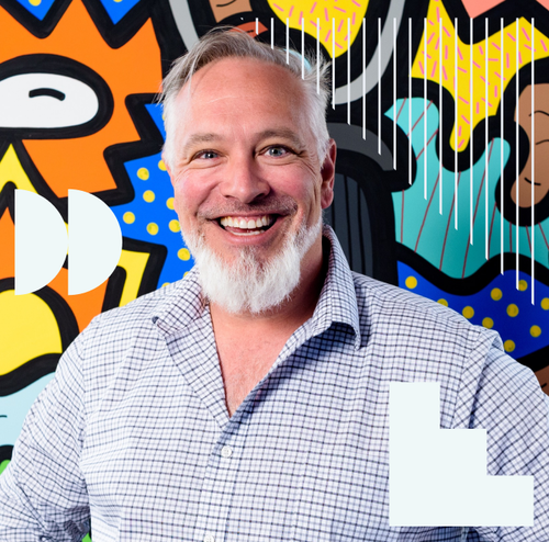 Derrick Mains, President and COO of Phat Scooters, smiling in front of a bright wall mural.