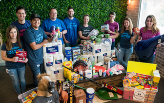 Nextiva Care's volunteers holding various donation supplies for Horses Help.