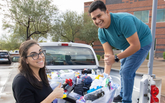 A couple Nextiva Care's volunteers loading up a pickup truck with socks.
