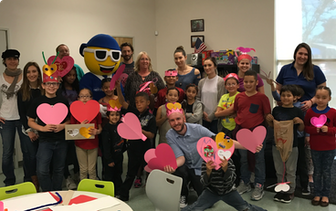 Nextiva Care's volunteers and youth posing while holding up hand crafted hearts.
