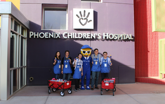 Nextiva volunteers underneath a Phoenix Children's Hospital sign.