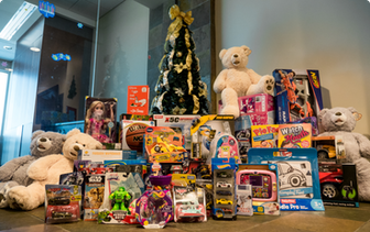 Toy donations stacked neatly around a Christmas tree.